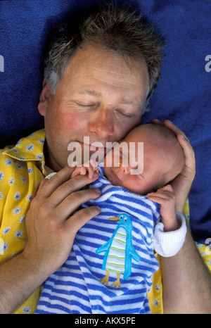 Glücklicher Vater schläft mit Neugeborenen Baby auf einer blauen Decke - Stockfoto