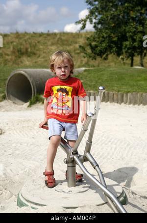 Drei Jahre alten Jungen auf ein Spielzeug Bagger - Stockfoto