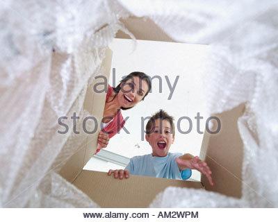 Frau und Jungen suchen in Karton lächelnd - Stockfoto