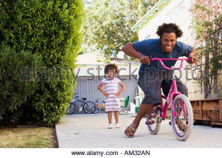 Vater Tochter Reiten Fahrrad in Einfahrt - Stockfoto
