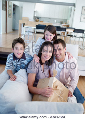 Mann und Frau mit jungen und Mädchen sitzen auf dem Sofa mit Paket - Stockfoto