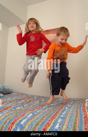 ein Junge und ein Mädchen auf einem Bett springen - Stockfoto