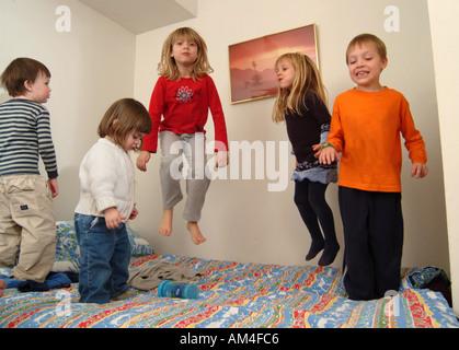 jungen und Mädchen spielen in ihrem Zimmer auf dem Bett springen - Stockfoto
