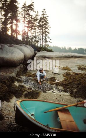 Frau auf einem felsigen Insel Strand in Maine. Sie hat an Land in einem Schlauchboot von einem Segelboot gesät. - Stockfoto