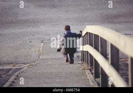 Kleiner Junge Klettern outdoor Treppe hinunter ganz alleine - Stockfoto