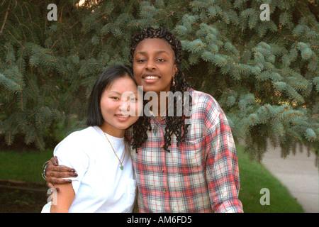 Asiatische und schwarze Freundinnen Alter 20 glücklich umarmen. St Paul Minnesota USA - Stockfoto