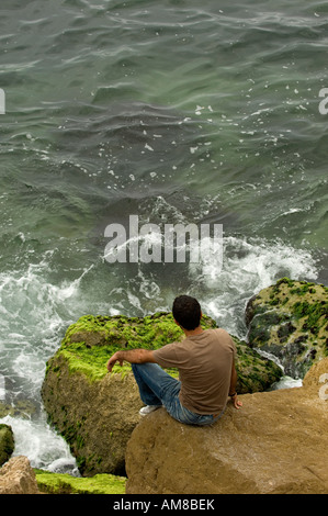 junger Mann sitzt auf den Felsen am Meer - Stockfoto