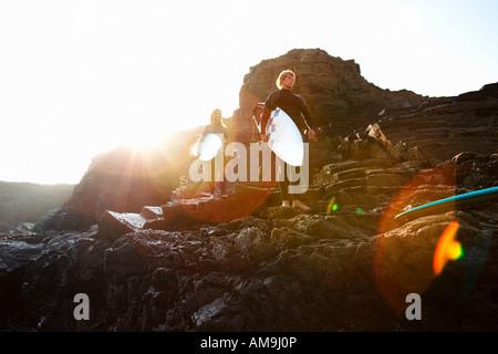 Paar auf großen Steinen mit Surfbrettern stehend. - Stockfoto