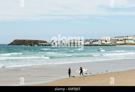 Zwei weibliche Surfer mit Surfbrettern zu Fuß aus Leistungsschalter auf dem West Strang in Portrush, County Antrim, - Stockfoto