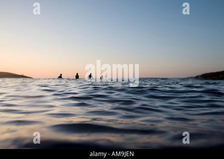 Vier Leute sitzen auf Surfbretter im Wasser. - Stockfoto
