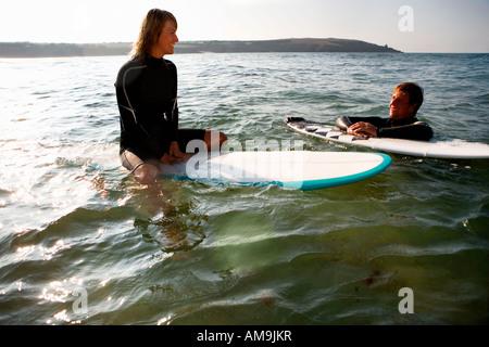 Paar schwimmt auf Surfbrettern in den Wasser-lächelnd. - Stockfoto
