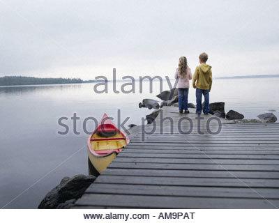 Junges Mädchen und Jungen auf einem Dock stehen in der Nähe von einem Boot. - Stockfoto