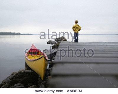 Junge auf einem Dock in der Nähe eines Bootes. - Stockfoto