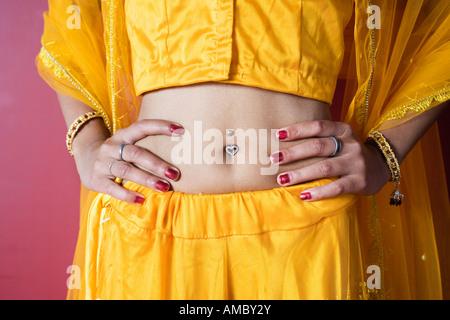 Mittelteil einer Frau mit gepiercten Nabel. - Stockfoto