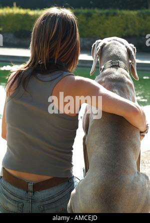 Weibchen mit Weimaraner Hund im Garten sitzen - Stockfoto