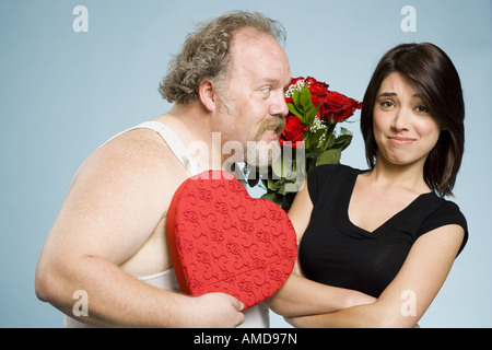 Zerzausten Mann mit Herz-Box und Rosen mit desinteressierten Frau - Stockfoto