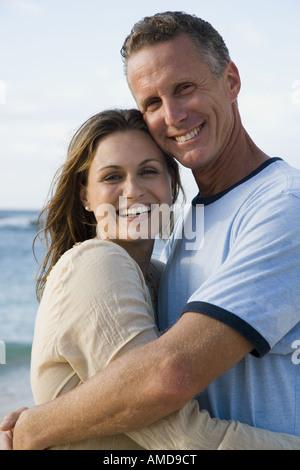 Mann und Frau im Freien am Strand lächelnd umarmen - Stockfoto