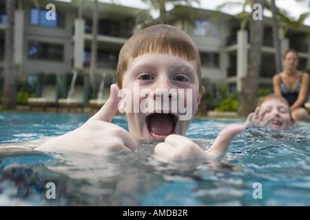 Junge im Außenpool machen lustiges Gesicht mit Daumen nach oben - Stockfoto