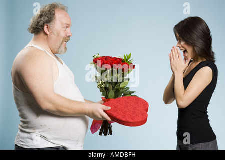 Zerzausten Mann mit Herz-Box und rote Rosen mit erregte Frau - Stockfoto