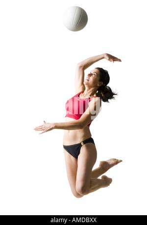 Frau im Bikini springen und Volleyball spielen - Stockfoto