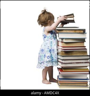 Junge Mädchen stehen neben Stapel von Hardcover-Büchern - Stockfoto