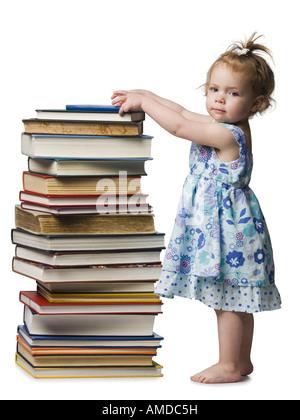 Junge Mädchen stehen neben Haufen von Hardcover-Büchern - Stockfoto