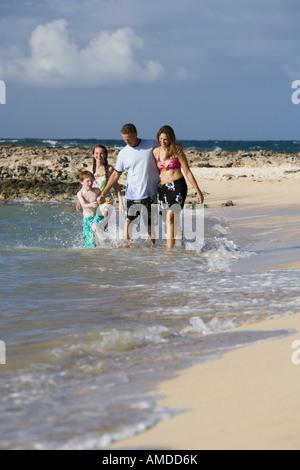 Paar mit jungen und Mädchen, die zu Fuß in Wasser am Sandstrand - Stockfoto
