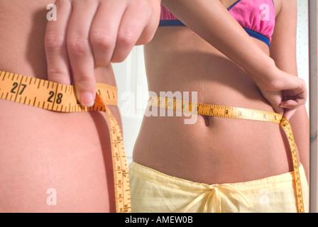 Nahaufnahme von Fingern und Maßband um die Taille eine schlanke weibliche s mit Spiegelbild - Stockfoto