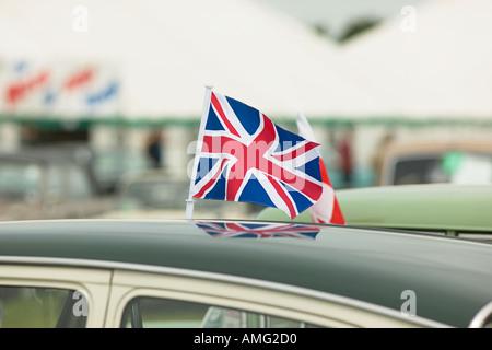 Union Jack-Flagge, die vom Dach des englischen Oldtimer vor Festzelt bei Rallye - Stockfoto