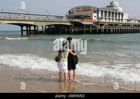 Asiatische fremdsprachige Studierende umarmen am Strand vor Bournemouth Pier, Bournemouth, Dorset, UK. Sept. 2006. - Stockfoto