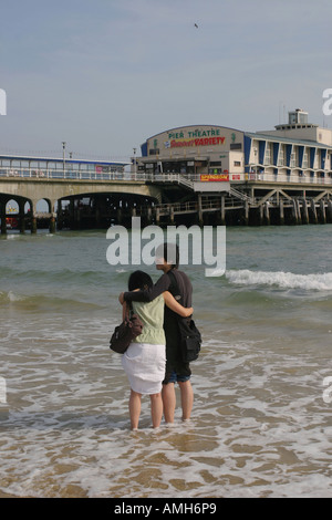 Asiatische fremdsprachige Studierende umarmen am Strand vor Bournemouth Pier, Bournemouth, Dorset, UK. Sept. 2006. - Stockfoto