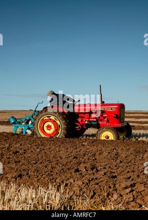Rote Vintage Traktor Pflügen Feld mit blauem Himmel - Stockfoto