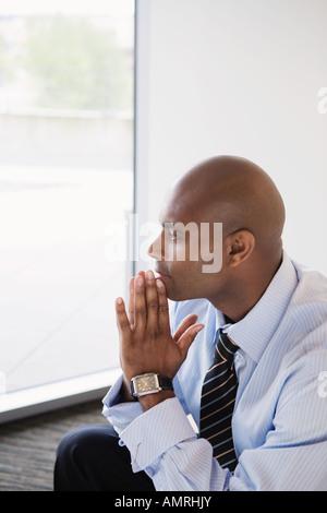 Afrikanischen Geschäftsmann Kinn auf die Hände ruhen - Stockfoto