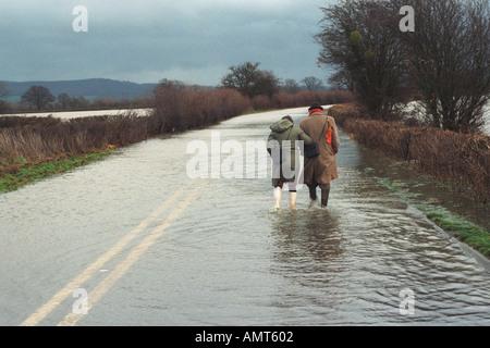 Älteres Ehepaar zu Fuß entlang einer überfluteten Straße in der Nähe von Hereford, nach dem Fluss Wye seinen Ufern - Stockfoto