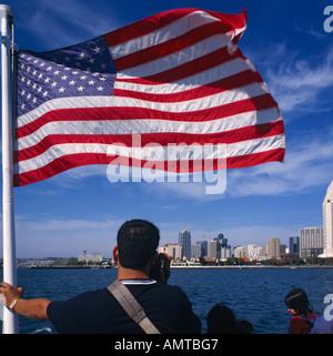 Menschen auf der Fähre Blick auf die Skyline der Innenstadt mit riesigen USA-Flagge im Vordergrund San Diego Kalifornien - Stockfoto