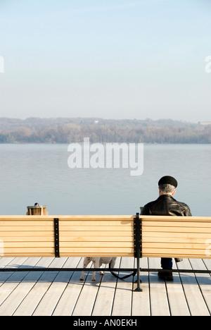 Mann in schwarzer Jacke und Mütze mit einem kleinen Hund sitzt auf einer Holzbank am Wasser auf einem Holzdeck. - Stockfoto