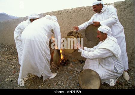 Vier Musiker stehen an einem Feuer und optimieren ihre Handtrommeln vor der Durchführung der Imilchil Bräute Messe - Stockfoto