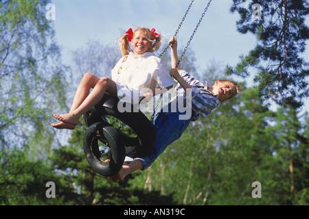 Jungen und Mädchen teilen zu schwingen an Sommertag in Schweden - Stockfoto