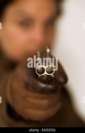 Unerkennbar Person mit dem Ziel, die Kamera mit einer doppelläufigen Pistole - Stockfoto