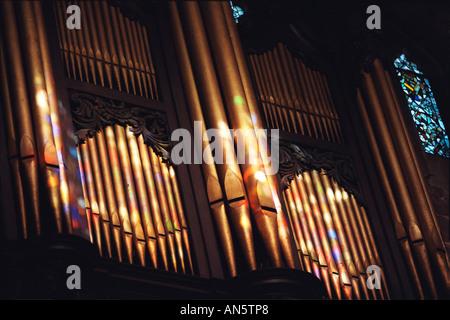 Farben von den Glasfenstern in Birmingham Kathedrale fallen auf die Orgelpfeifen als Sonne durchscheint. - Stockfoto