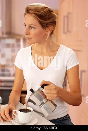 FRAU IN DER KÜCHE GIEßEN KAFFEE - Stockfoto
