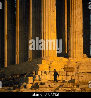 Single Mann gekleidet in dunkle Kleidung auf Stufen des Parthenon mit der Sonne wirft einen goldenen Schimmer auf - Stockfoto