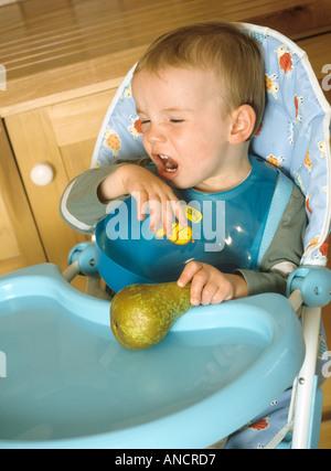 Kleiner Junge sitzen in einen Hochstuhl, der sich weigert zu essen eine Birne - Stockfoto