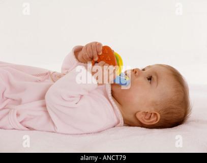 Babymädchen liegen auf dem Rücken, kauen auf einem Plastikring Zahnen - Stockfoto