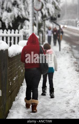 Frau mit Handtasche und junges Mädchen zu Fuß bergauf auf Schnee überdachten Fußweg - Stockfoto