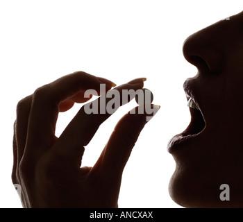 Frau, die eine Pille-Silhouette - Stockfoto