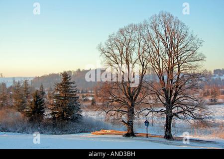 Sonnenuntergang auf einem kalten Winter Tag Weg entlang am Straßenrand Kreuz und Protokolle zwischen Bad Tölz Lenggries - Stockfoto