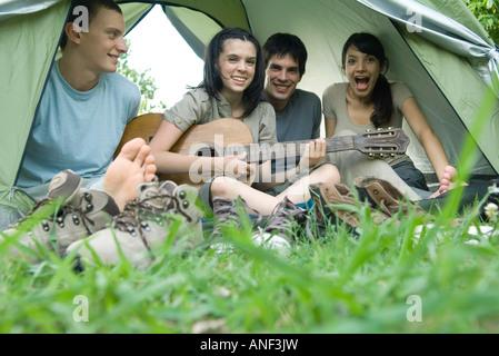Freunde im Zelt zusammen, Teen Mädchen spielt Gitarre - Stockfoto
