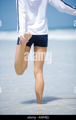 Junge Frau am Strand, Dehnung - Stockfoto