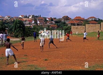 Gruppe von jungen & Jugendlichen Acholy Elendsviertel shoeless Fußballspielen durch Wohngebiet Kampala-Uganda-Ost - Stockfoto
